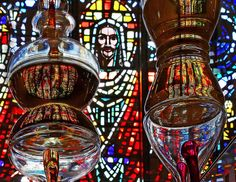 Reflections of baptimsal oil sitting on a mirror in a glass case at St. Thomas Aquinas by R.J.E., via Flickr