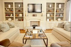 this is how the fireplace wall of our living room is set up.  exits on either side so couch placement would not work.  love the simplicity of the stuff on built ins- NOT cluttered!