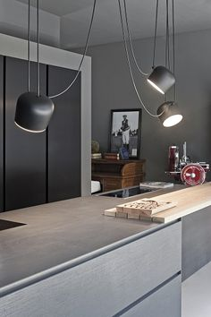 The FLOS AIM modern pendant lights add a warm glow to this kitchen interior with muted grey coloring.