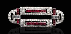 AN ART DECO RUBY AND DIAMOND BROOCH The geometric openwork plaque, set with old European and baguette-cut diamonds, accented by calibré-cut rubies, mounted in platinum, circa 1925