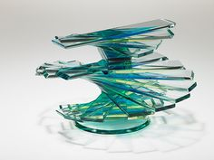 """Helix Solid Vase Form #16. 2009.  7""""x9.5""""x5.25"""".  Designed and fabricated by Sidney Hutter.  This fine art glass sculpture was created by laminating (dye mixed into the adhesive) cut, ground and polished 1/4"""" glass bars together in a helical pattern to form the silhouette of a vase."""
