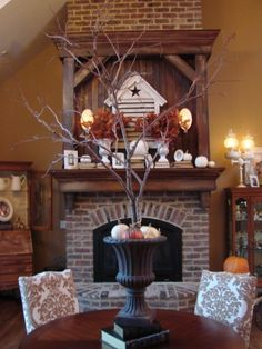 I need one of these!  She got a fallen limb and put it in a bucket w/plaster of paris, then put the bucket inside the urn... great to use for any season (hang ornaments, icicles, photos, whatever)....for fall here she's added baby pumpkins and straw at the base.