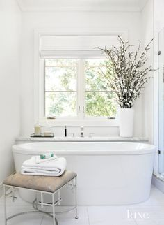 A freestanding tub by Victoria + Albert tucks into a niche in this bathroom, featuring ample amounts of natural light and views of a garden through a shade from Curtain Call. An upholstered stool by Worlds Away provides a warm contrast to the Calacatta gold marble used throughout the space. #LuxeTurns10
