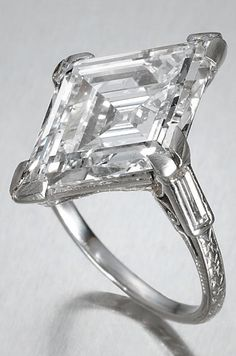 An early 20th century diamond single-stone ring, circa 1915. The step-cut lozenge-shaped diamond, weighing 5.92 carats, to a four double-claw mount with baguette-cut diamond shoulders, the hoop with engraved foliate decoration. #BelleEpoque #ring