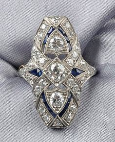 Art Deco Platinum and Diamond Ring, set with old European-, and single-cut diamond melee, further set with fancy-cut blue stone highlights, millegrain and engraved accents