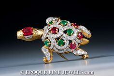 CARTIER A magnificent ruby, diamond and emerald turtle brooch, designed as a diamond and textured gold turtle, with emerald and ruby highlights, mounted in platinum and 18 karat gold.