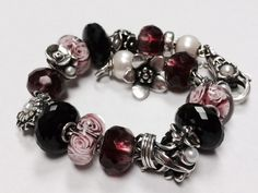 Floral-themed Trollbeads bracelet with pink, burgundy, black and pearls.