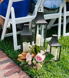 aisle markers for this lakeside wedding were a trio of lanterns dressed with a cluster of pink blush roses, cream spray roses, seeded eucalyptus and magnolia.