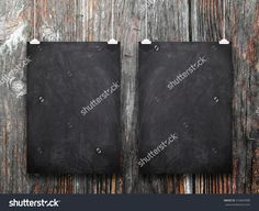 Two blank black blackboard frames hanged by clips against old weathered wooden boards background