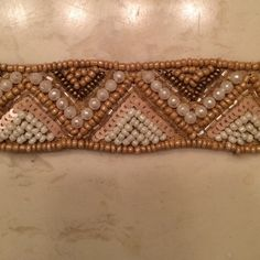 Neutral White Cream Gold Beaded Belt with Tie Purchased from boutique but never worn. Has been in closet since purchased. Beautiful colors. Measures a little over 27 inches. Does not have any stretch to it. Ends of belt have ties. All beads in tact. Would keep it but I don't have any use for it! Accessories Belts