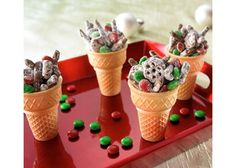 These are ice cream cones with some chocolate covered pretzels and m&m's all covered some flour or confectioners sugar.