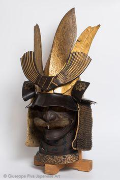 """Elmo da samurai a forma di copricapo scintoistaMetà del periodo Edo (1615 - 1867), XVIII secolo Il disegno di questo spettacolare elmo (kawari kabuto) interpreta la forma dell'eboshi, il copricapo di corte tipico dei preti scintoisti. Costruito con cinque piastre di ferro rivettate, è ricoperto con una lacca dorata finita in rilievo e porta sul retro un """"ken"""" rosso sbalzato all'interno. Sul davanti, tre tsunomoto (supporti per decorazioni) reggono un raro triplo maedate dorato. Samurai Helmet, Helmet Armor, Samurai Warrior, Arm Armor, Japanese Mask, Japanese Warrior, Samurai Artwork, Chinese Art, Chinese Painting"""