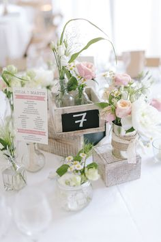 Shabby chic wedding centerpieces with burlap wrapped vases and spring florals. Tiny chalkboard signs used as table numbers.