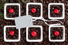 close-up shot of coffee beans and empty placard. - Close-up shot of coffee cups full of coffee beans with red candies and empty placard.