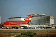 Braniff International Boeing 727-227/Adv N430BN taxis onto the threshold of Runway 24L with the Hyatt Hotel looming in the background at Los Angeles International, August 1980.