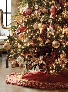 Rich burgundy and gold fabrics accented with glistening pearls make the Belissima Tree Skirt sparkle.