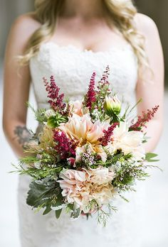 A rustic bouquet comprised of dahlias, protea, wax flowers, and astilbe, created by Not Just Flowers.