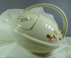 HALL CHINA JEWEL TEA/AUTUMN LEAF FOOTBALL TEAPOT - 1995 HALL Autumn Leaf Football Teapot, this teapot was made exclusively for China Specialties by Hall China Company in 1995. It has the beautiful Autumn Leaf Motif on each side and is gold tr...