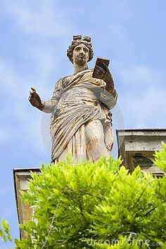 Antique female statue as ornament on the roof of an old building in Brasov city, Romania.