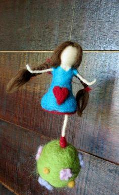 Boneca feltrada correndo sobre uma bola com flores