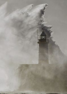 Waves crash against a lighthouse at Newhaven in South East England Oct 2013
