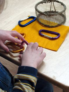 Hooking together caribiners. Clipping carabiners: a great way to improve dexterity while working on a Practical Life task that's inexpensive to put together. As skills grow, you can switch out the activity to screw carabiners.