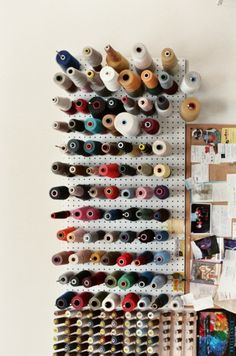 A peg board and some long nails/pegs are a great way to keep thread easily organized and at an arms reach.
