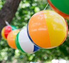 string up a series of beach balls for bright decor for a pool party.