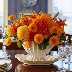 Orange Flowers Centerpiece-A footed white dish is both fancy and festive when filled with an array of orange-hue flowers. Use florist's foam to hold the arrangement securely in place.  Editor's Tip: Slip a few black roses into the mix, or place miniature pumpkins at the base of the decoration -- painted black if you'd like -- to make the orange flowers really pop in this Halloween centerpiece