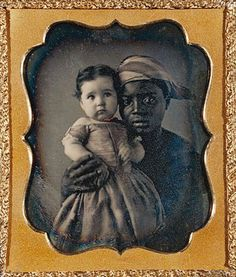 +~+~ Antique Photograph ~+~+   Young African American woman with a steady loving gaze, tenderly holding her charge.  ca. 1850