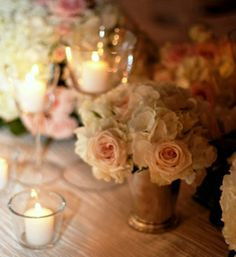 trios of silver mint julep cups filled with cream hydrangeas, pale pink spray roses, white anemones, and grey dusty miller surrounded by silver rimmed champagne flutes with floating candles and mercury glass votives