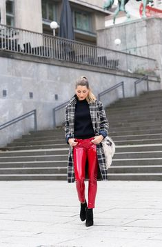Stephanie Van Klev wearing a pair of red latex trousers paired with black high heeled booties.