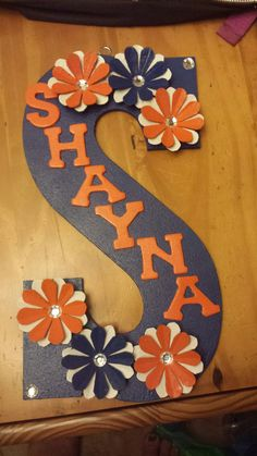 this is a wood letter wall hanging using smaller wooden letters for the name and egg carton flowers with rhinestones