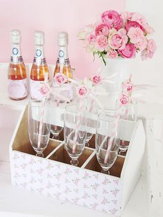 Champagne flutes are displayed inside a vintage bottle crate (a great flea market find) and decorated with printable scrapbook paper. Striped paper straws also get dressed up for the occasion with a ribbon flag and paper rosebud accent (from craft stores) — all in keeping with the pretty and romantic theme of the day.