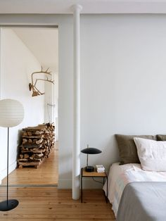 Bedroom in Paris loft invitingly layered with pale pastel sheets & linen-covered pillows.
