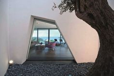 The window of this modern house is geometric in shape, and provides a ground level glimpse of the interior.