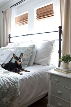 Bed against window, and how to resolve the pretty v. functional conundrum for bedroom curtains.Layered window treatments: Roman shades to block light, sheer curtains