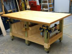My 4 x 6 ft woodworking assembly table. Six legs from 4 x 4 posts, each   with locking wheels. Table top is made from two sheets of 3/4 inch Birch plywood with 3/4 inch Oak trim.  Finish is high gloss Tung oil.  Lots of   nooks & crannies for tools, glues, paints, clamps.