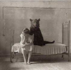 Ένας κορίτσι με μια αρκούδα στο κρεβάτι.