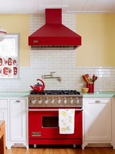 COLORFUL CONTRAST With cheerful, red appliances and mint green granite countertops, white subway tile provides the perfect contrast in this retro-themed kitchen.