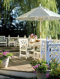 Chippendale white patio railings, striped cushions and umbrella.