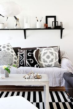 Fresh boho chic living space. Cute paisley print throw pillows and lovely concrete coffee table with built in tea light candle holders! Monochrome really works in this space.