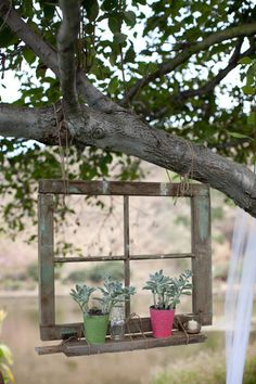 An old window hung from a tree adds interest to the garden.
