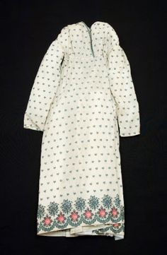 1812-15 Snowshill Manor © National Trust / Simon Harris  Dress - An early 19th century (1812-1815) dress of very fine cream cotton, with all over spot design of flower and leaf brocaded in tartan green. Deep border at hem - very finely woven design of loose bunch of flowers and naturalistic rose and rosebud. Scalloped edging line in lace design. Border worked in tartan green and calret red. Borders on bodice of fabric woven with scalloped 'lace' design matching the dress fabric, to be cut…