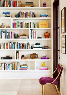 Colorful, nicely organized bookshelves.  Nice balance of books and pretty things.