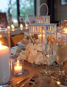 Over-sized white lanterns with flowers and votives as a wedding reception centerpiece.