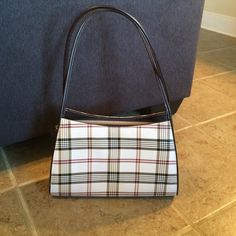 Brown and plaid print purse Carried a few times brown plaid purse. Purchased in New York City on vacation. Has a structure handle. Zips closed and has a zippered pocket inside. 12 inches across and 7 inches long. The handle drop is 11 inches. Bags