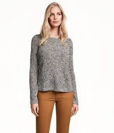 Rib-knit sweater with wool content. Flat-knit back section. Slits at sides and at cuffs. Slightly longer at back.