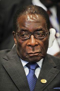 """Robert Mugabe Millioner af døde: 1,2 'Afrikas Juvel' Zimbabwe, bombet tilbage til stenalderen. R.M. lader en pøbel ledet af Chenjerai """"Hitler"""" Hunzvi myrde løs på hvide farmere. 25 % af Zimbabwianere er HIV-positive. Gnmsn. levalder faldet til 16 år."""