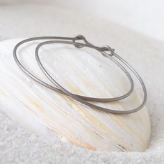 These hoop earrings are made with pure, grade one titanium wire. Titanium is a mat gray metal. It is a very strong wire and hypoallergenic.